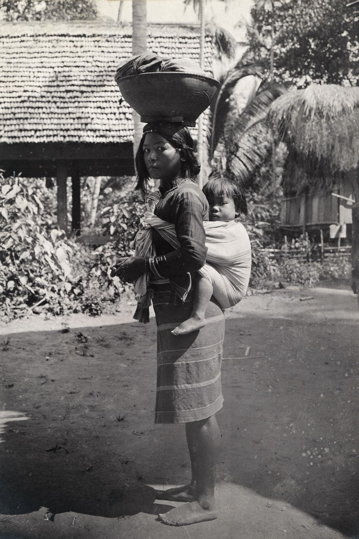 A Tingian woman carries a child on her back and balances a basket on her head ...