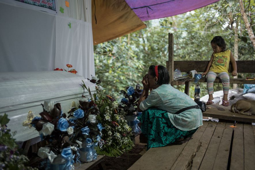 An elderly mourner sings a traditional ngulngul, or sorrowful song, in front of Joy Tudo's casket.