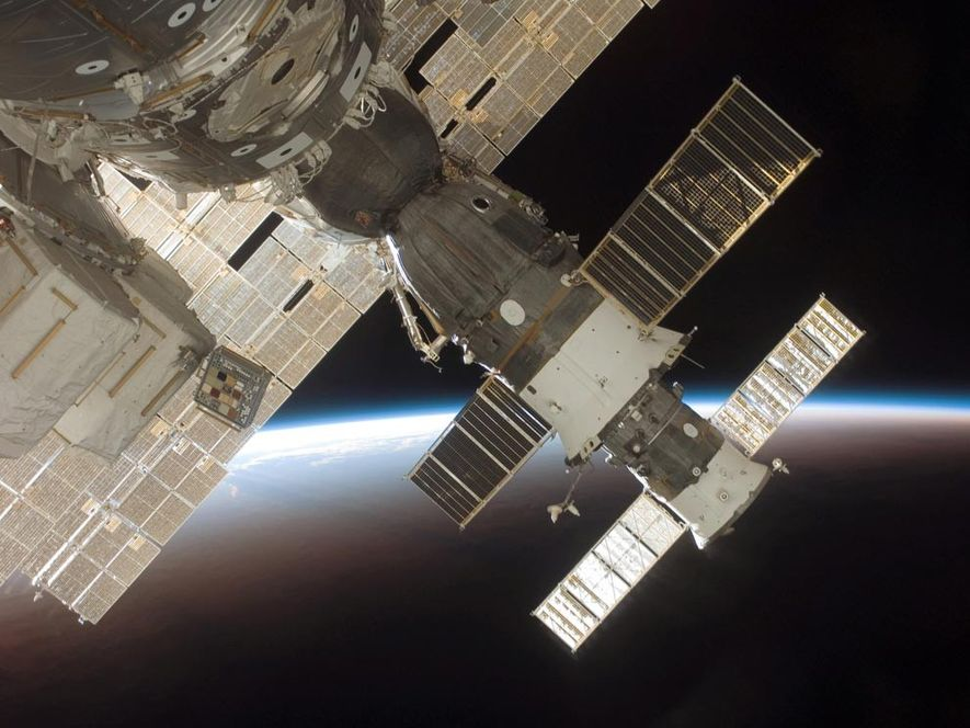 The blackness of space and Earth's horizon provide the backdrop for this image of the docked ...