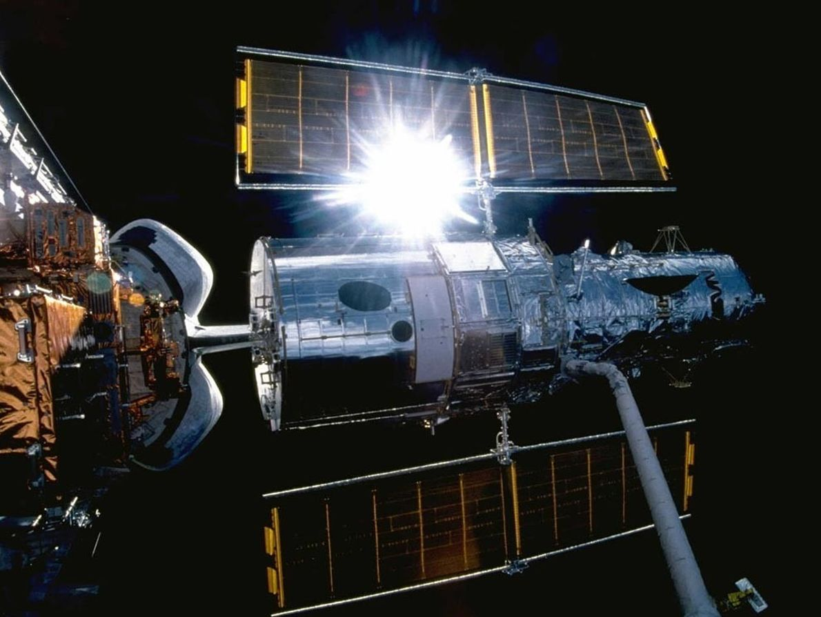 Sunlight glints off the Hubble Space Telescope as it sits suspended over the cargo bay of ...