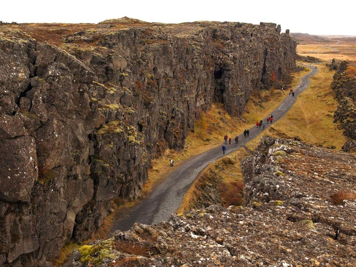 Hikers walk in the shadow of cliffs in Iceland's Thingvellir National Park. The divergent Mid-Atlantic Ridge ...