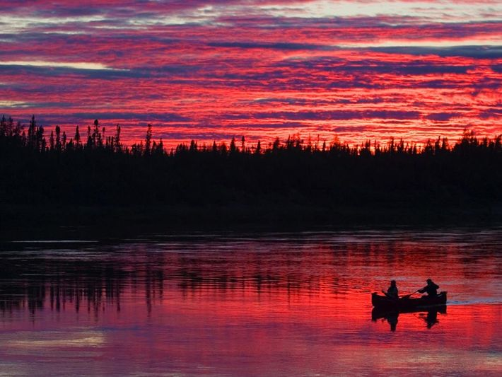 Colourful clouds and calm water create a striking sunset scene for canoeists on Winisk River in ...