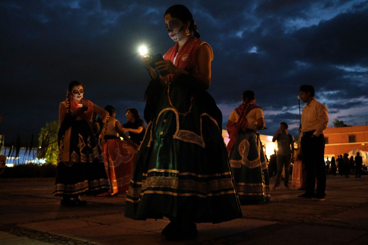Parade participants take a break at the Day of the Dead festival in Oaxaca, 2018.