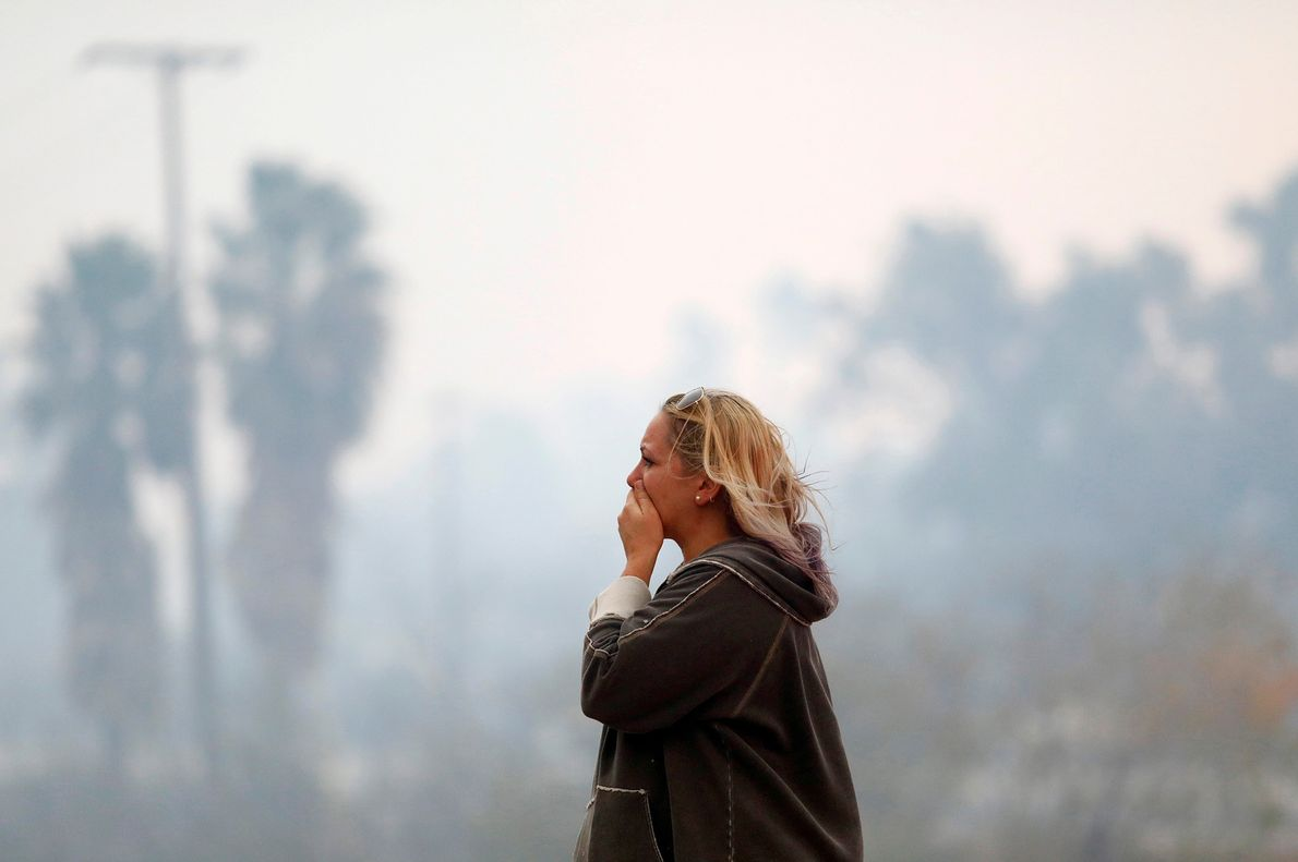 A woman takes in the Woolsey Fire burning in Malibu, California. The fire destroyed dozens of ...