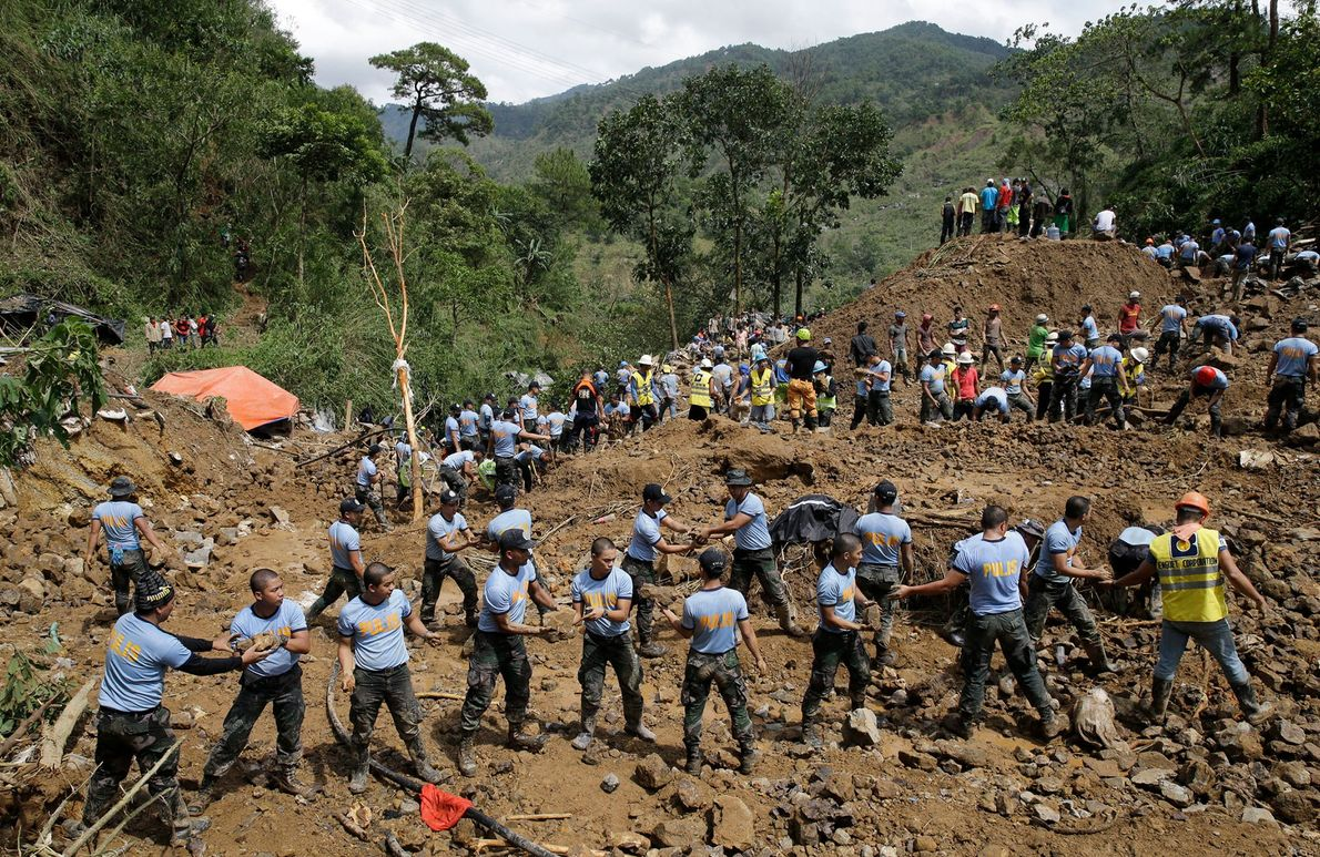 Rescuers move stones at the site where victims are believed to have been buried by one ...