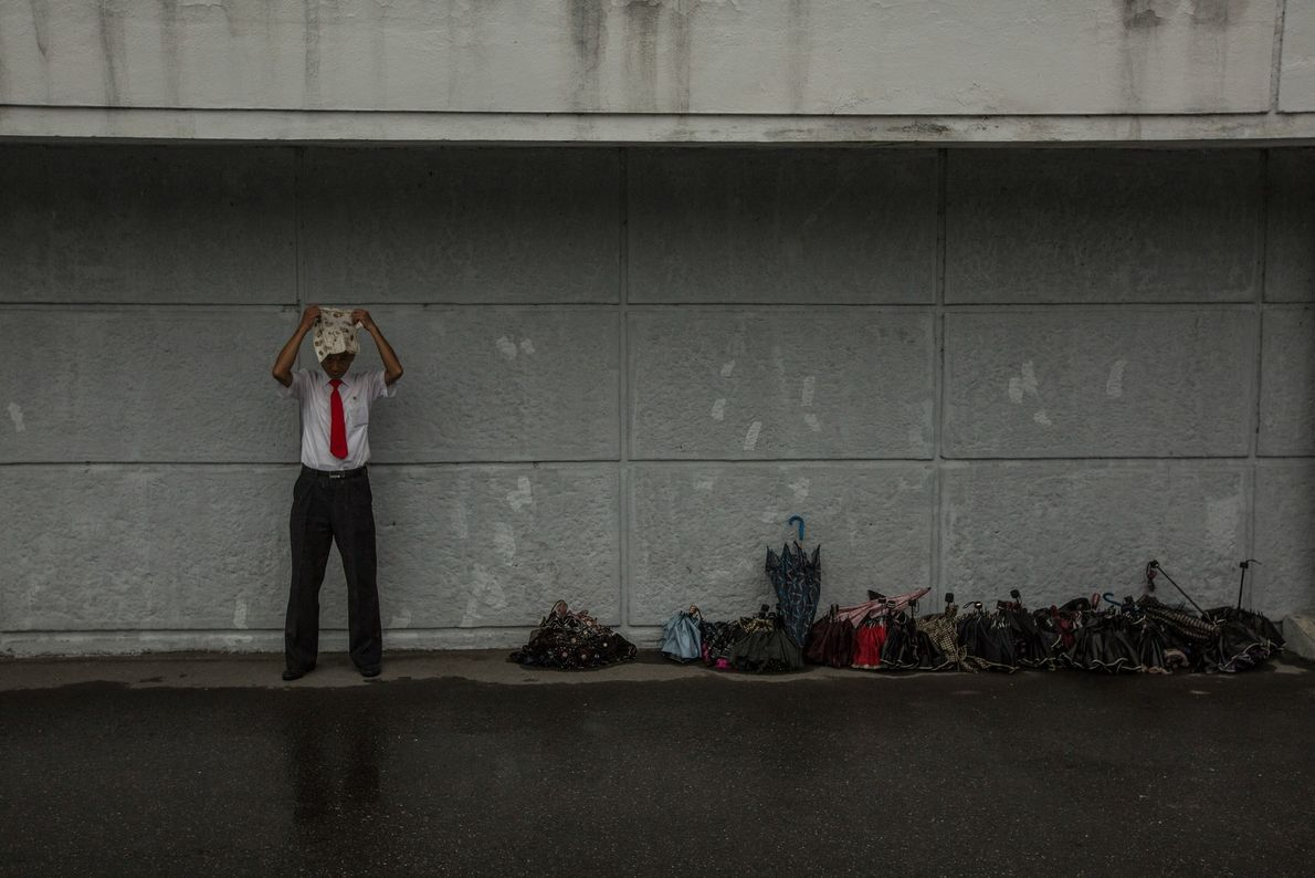 A man places a handkerchief over his head to protect himself from the rain as he ...