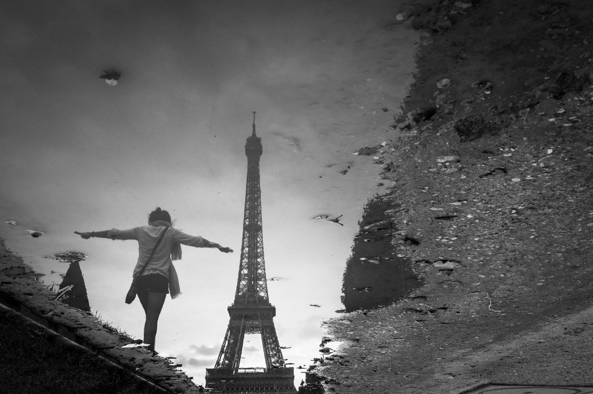 An image of the Eiffel Tower reflects off a puddle in Parc du Champ-de-Mars, which extends ...