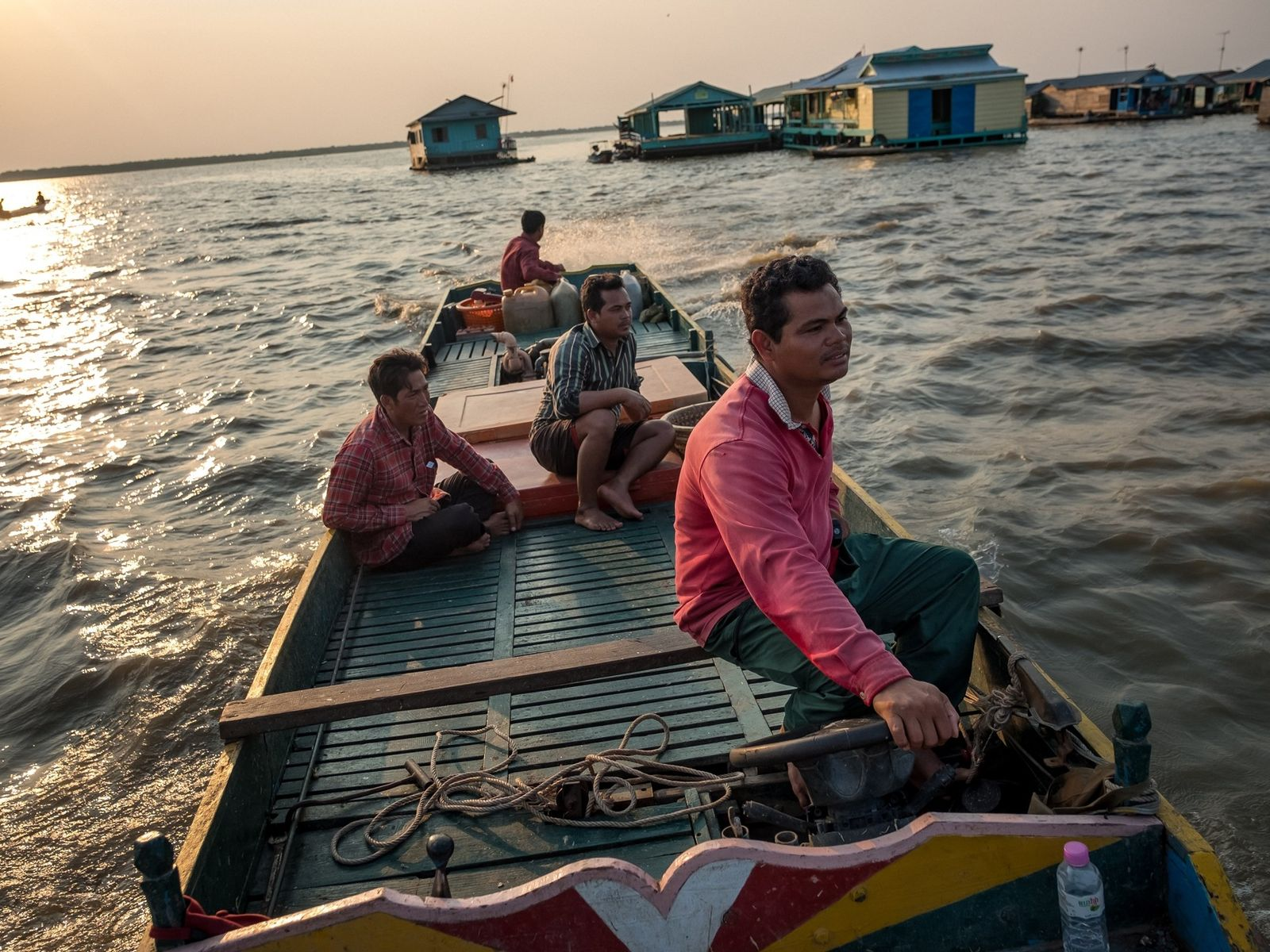 A fishermen drives past a floating village on Tonle Sap Lake. Many residents that live on ...