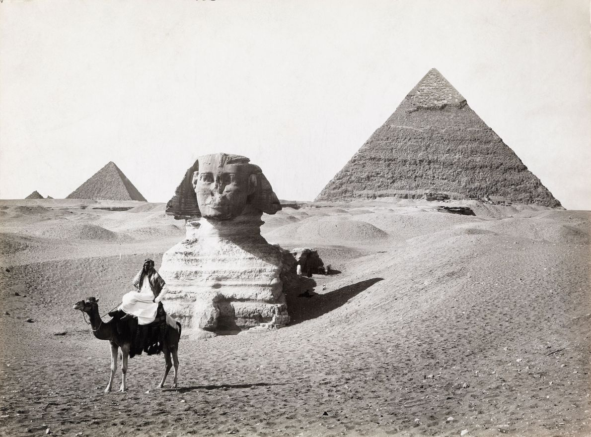 A man poses on a camel in front of the Great Sphinx and pyramids of Giza.