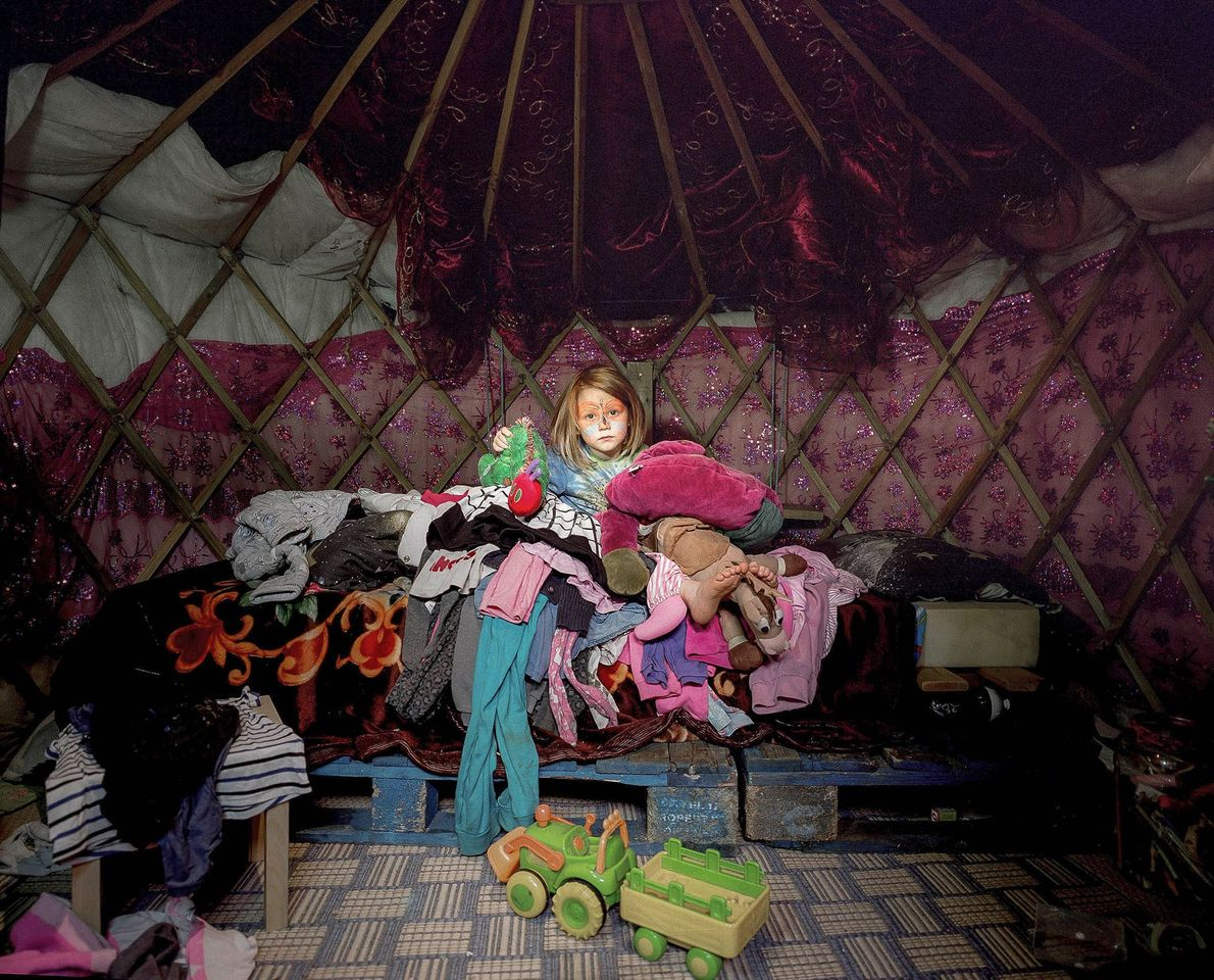 A five-year-old girl sits in the yurt she shares with her father. After spending much of ...