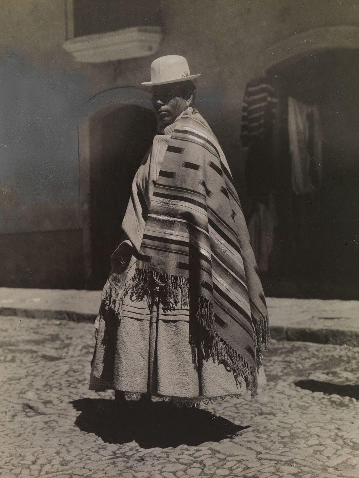 A mestiza girl in a white bowler-style hat, a headpiece often worn by indigenous Bolivian women, ...