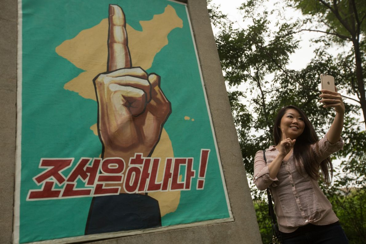 U.S. tourist Amy Kang takes a selfie photo at a propaganda monument in Panmunjom, North Korea ...