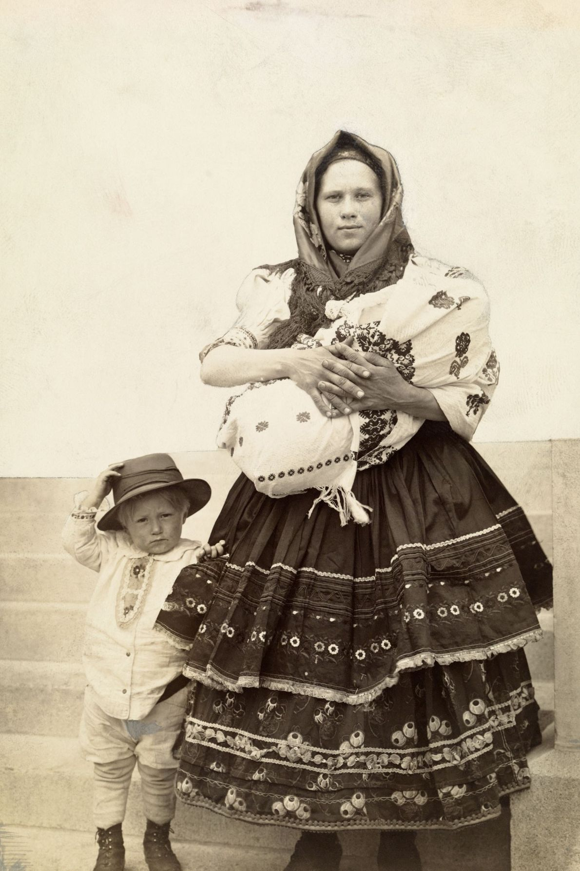 A Slovak Hungarian immigrant to the United States holds her infant and stands by her son.