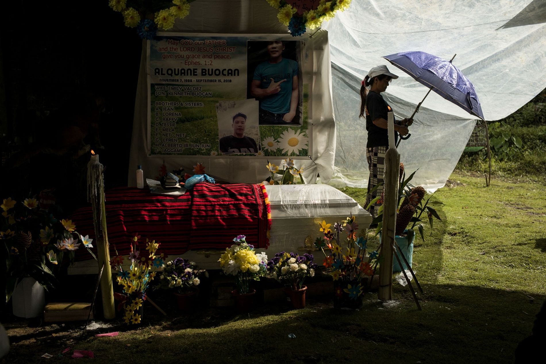 A banner above Buocan's casket includes a verse of Christian scripture and the names of his ...