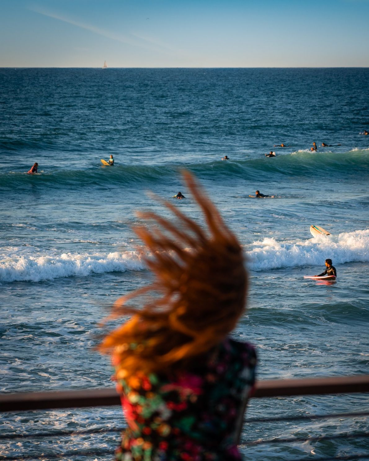 """""""A woman dances to a street performer's music while surfers surf and the sun sets in ..."""