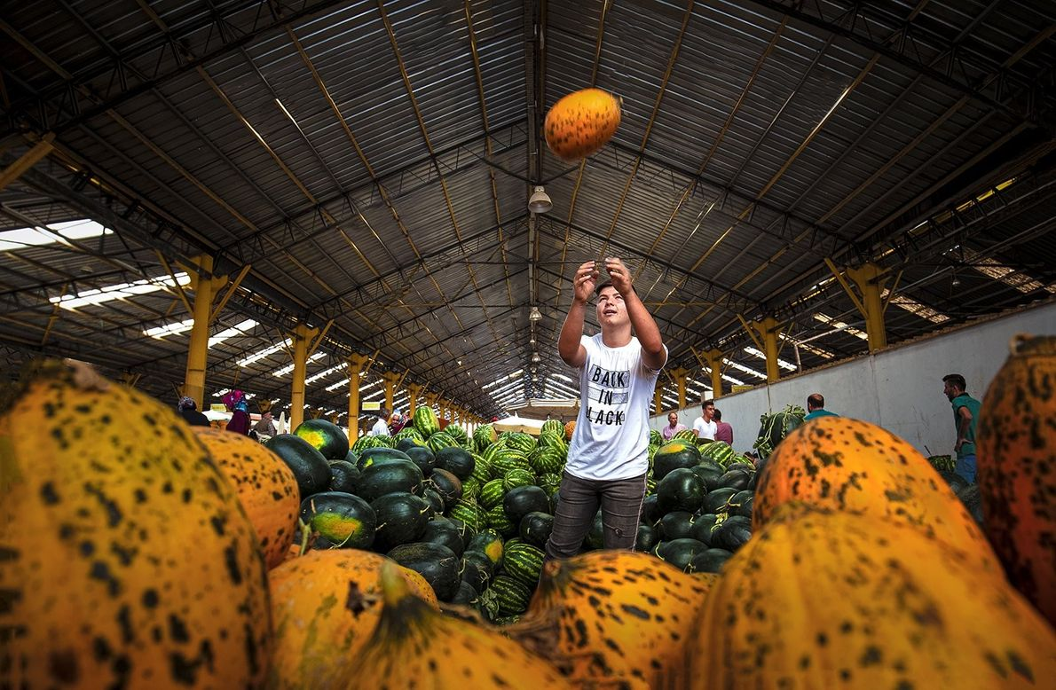 A melon seller tosses a fruit in the air of a bazaar in Turkey.
