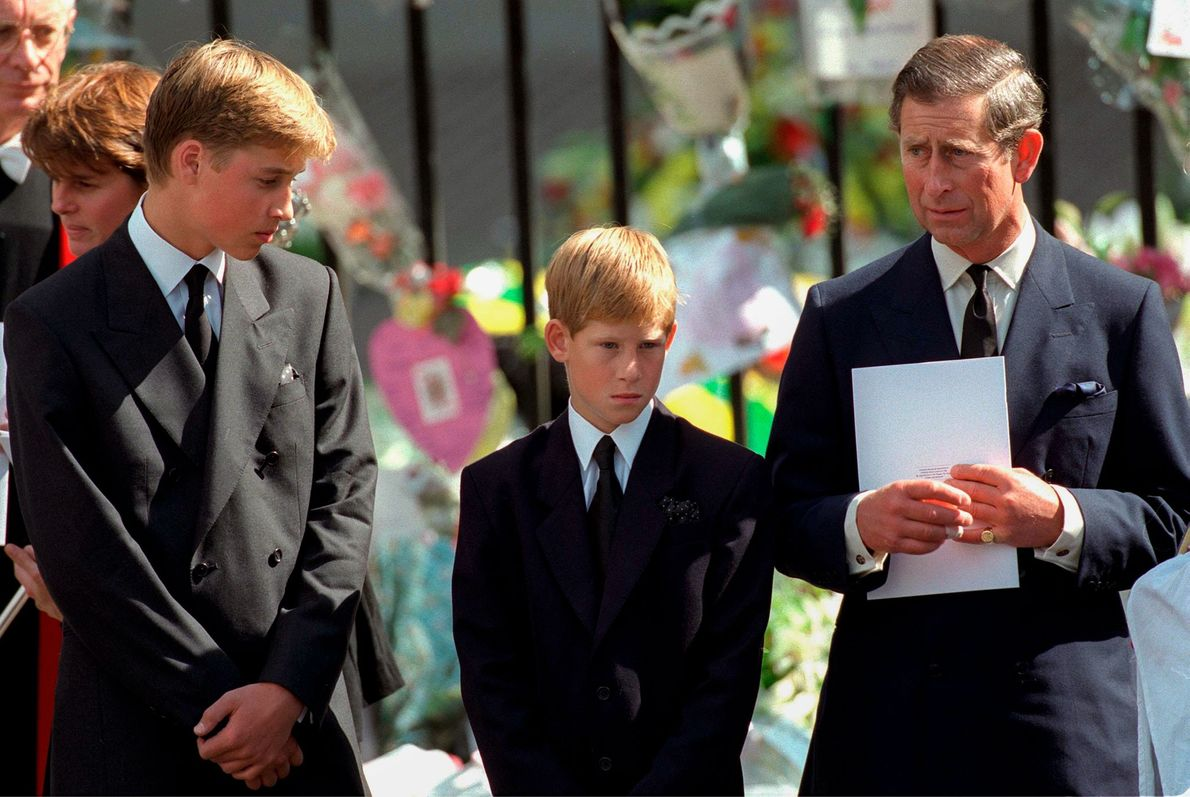 Standing with sons Prince William and Prince Harry, Prince Charles holds a program at the funeral ...