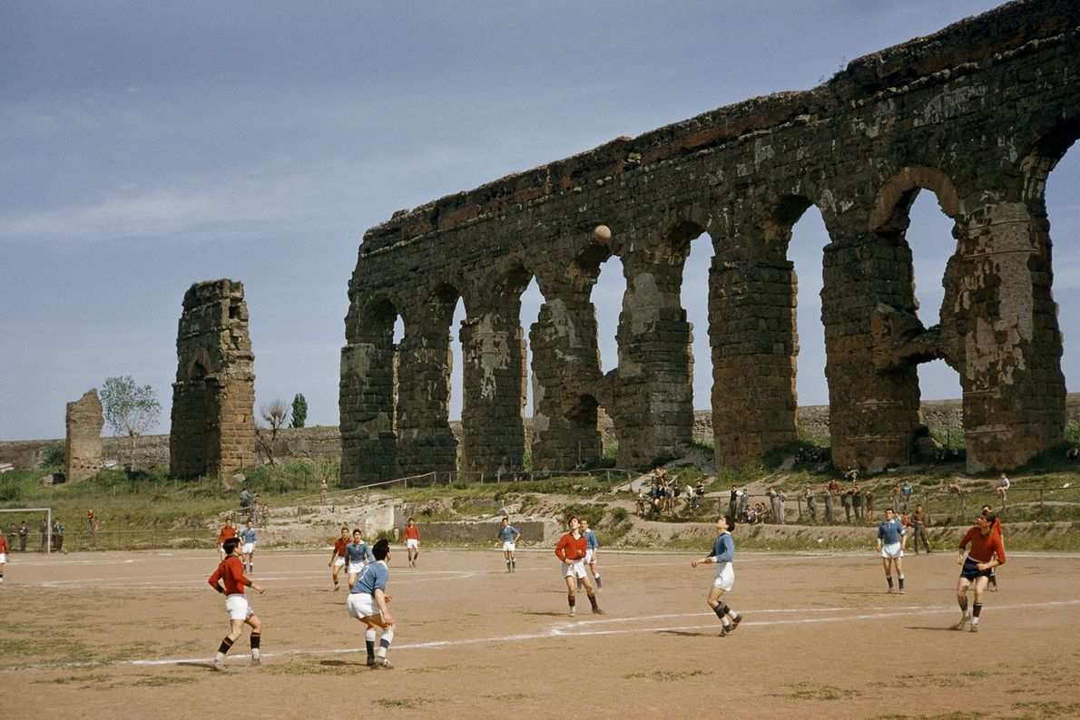 In 1957, boys play soccer beside arches of an ancient aqueduct in Rome, Italy.