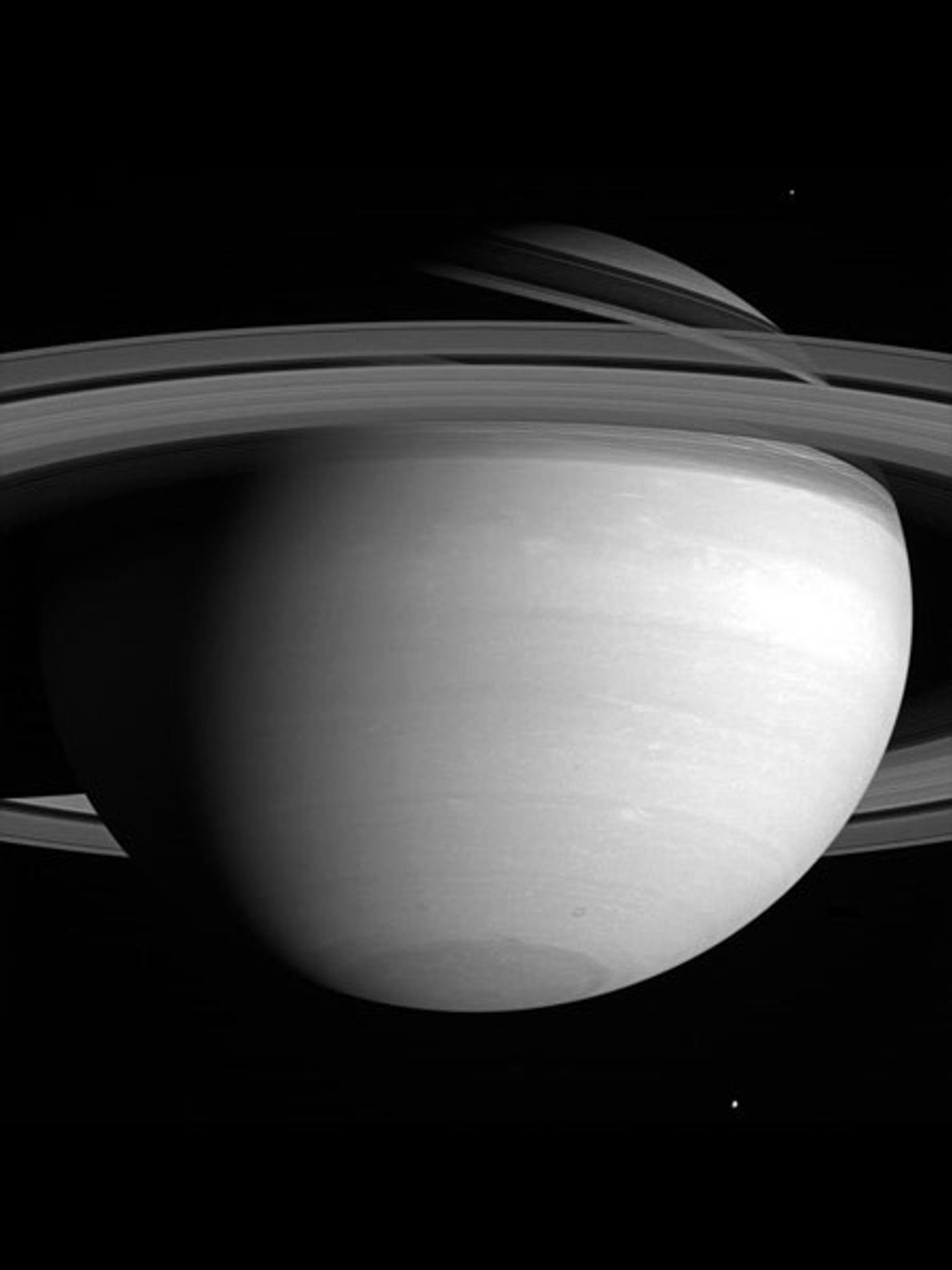 Two of Saturn's more than 60 known moons are barely visible in this picture of the ...