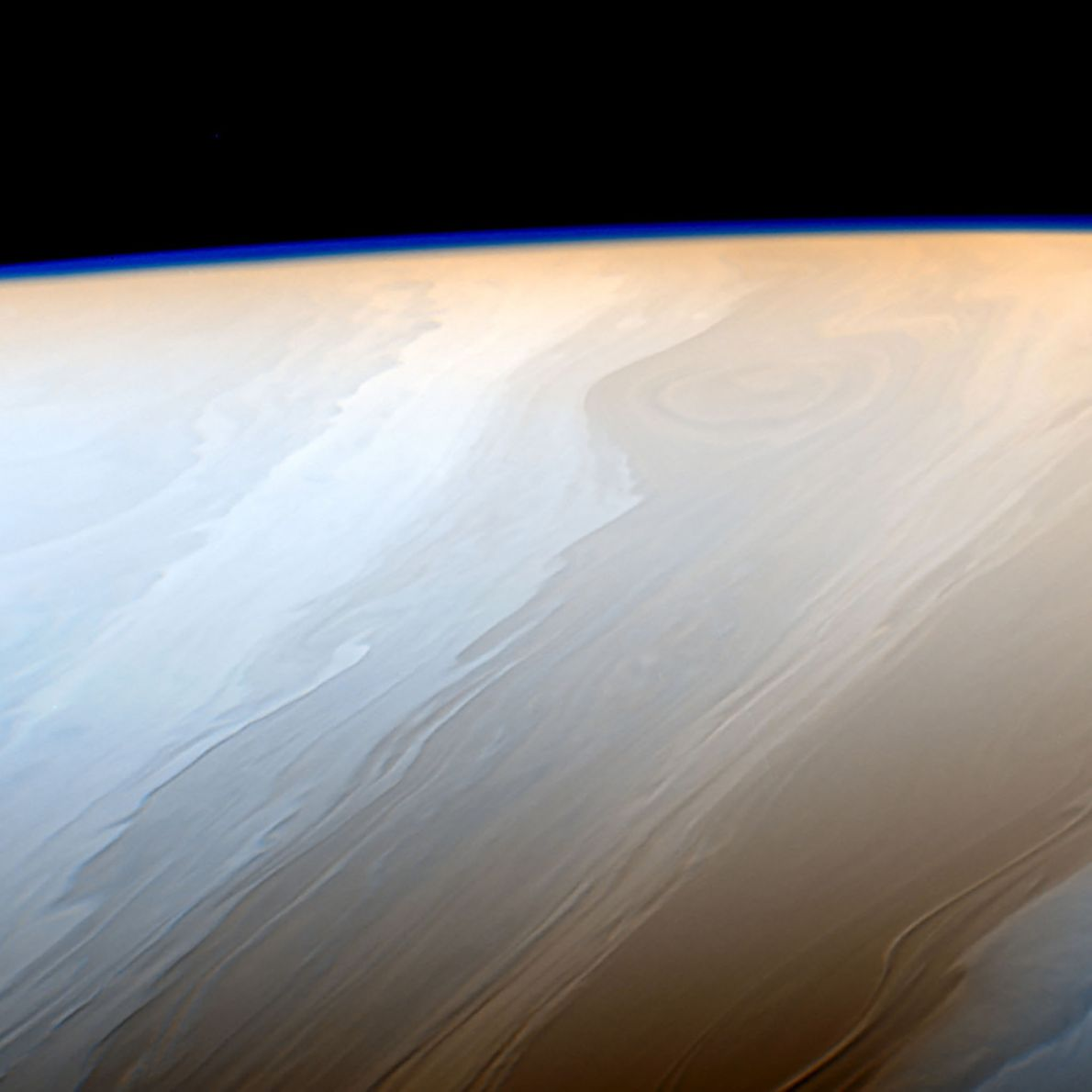 Saturn's upper atmosphere generates the faint haze seen along the limb of the planet in this ...