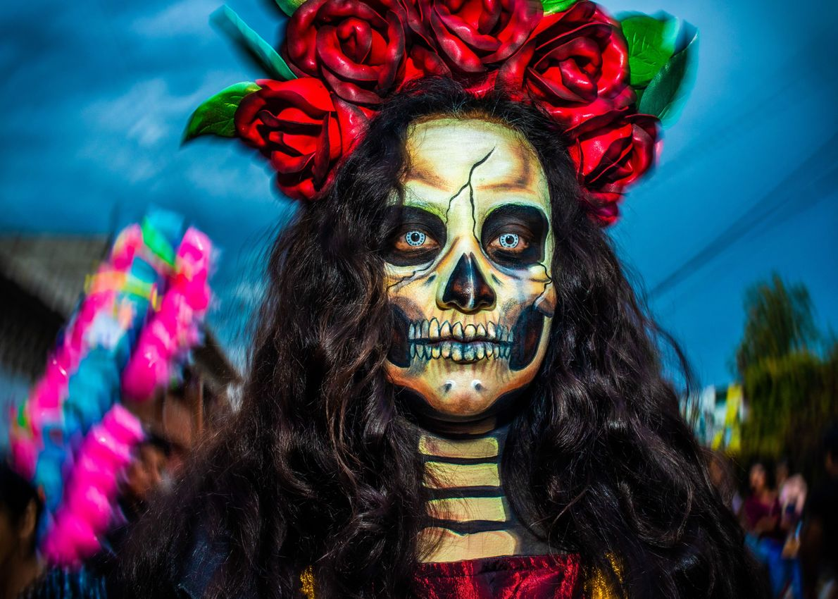 A woman in elaborate sugar skull makeup, Day of the Dead Festival, Oaxaca 2018. According to …