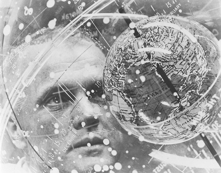 John Glenn peers into the 'globe within a globe' Celestial Training Device.