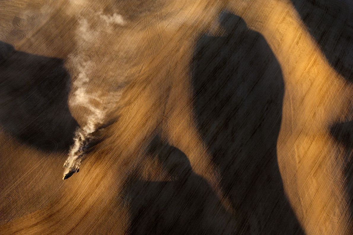 A harvester rumbles across the Palouse of Washington, an area of loess hills made of wind-blown ...