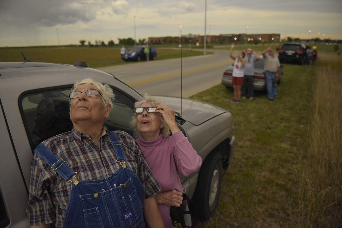 Wilfred and Audrey DeVries try to watch the eclipse through cloudy skies along with others who ...