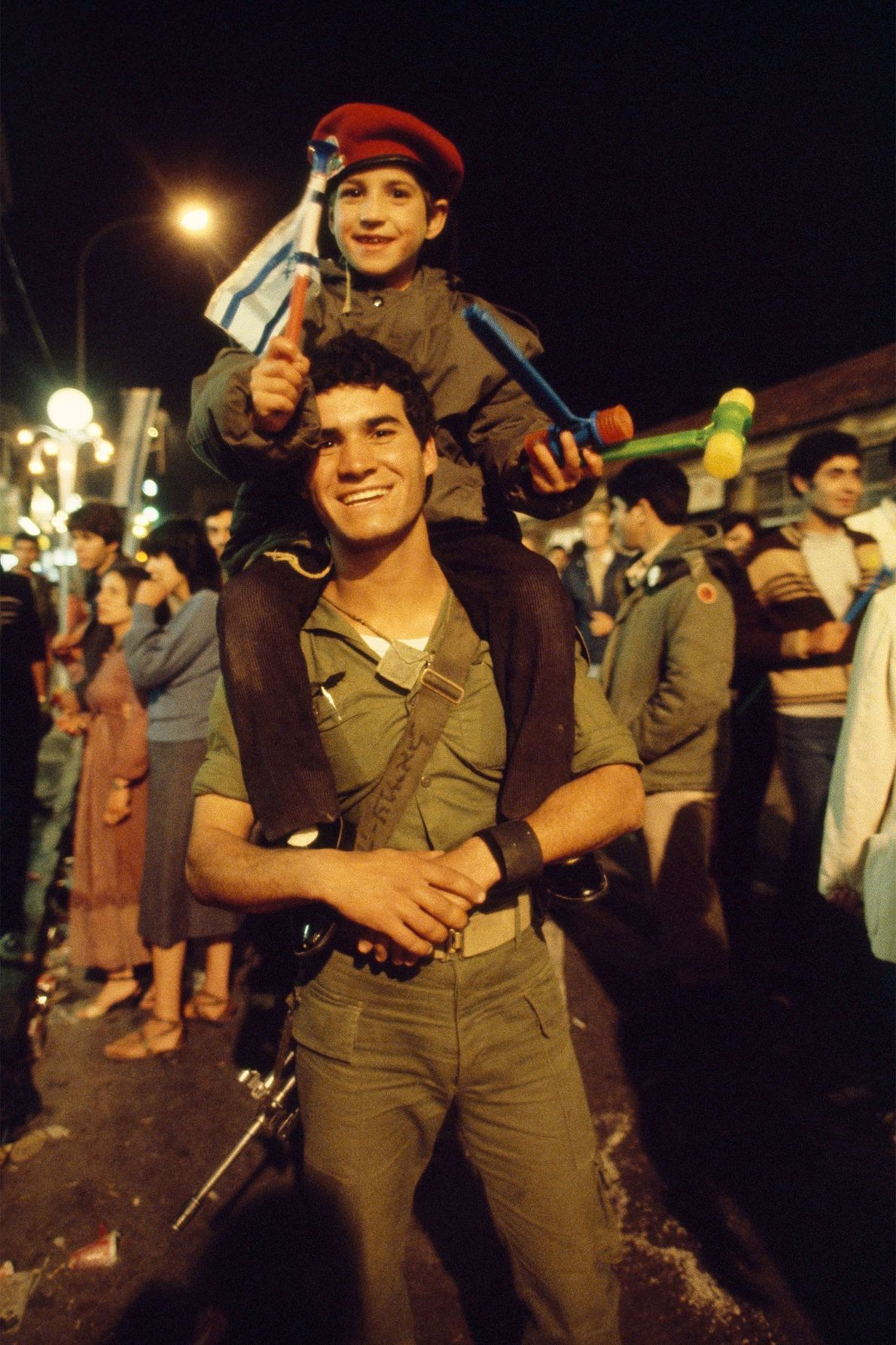 An Israeli soldier in Jerusalem holds his flag-waving son on his shoulders during Independence Day celebrations ...