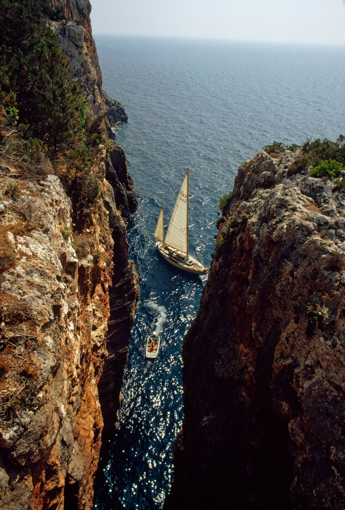 Boats cut through the epic cliffs of Cephalonia.