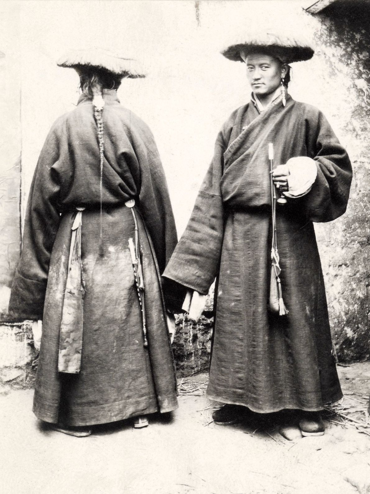 Attendants to an official in Lhasa, Tibet, wear wool hats and rings in their ears.