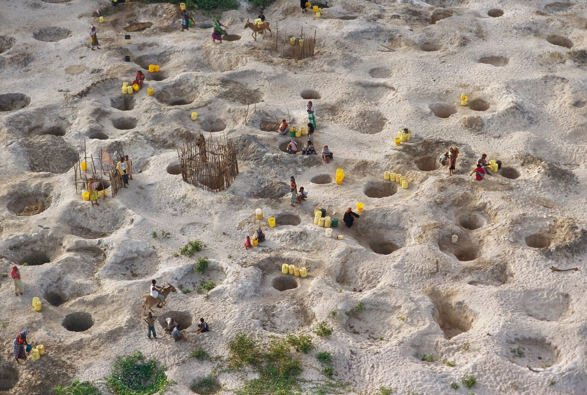 Villagers gather brackish drinking water from shallow wells within a hundred yards of the ocean on ...