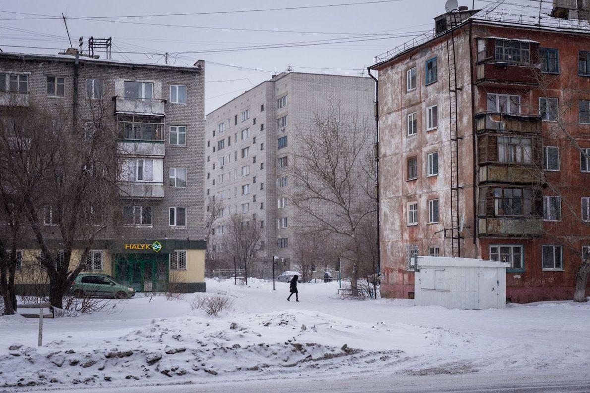 A woman walks through Soviet-era housing blocks in Semey.