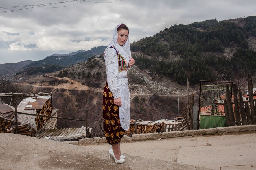 Wearing traditional dress, a young woman in Ribnovo makes her way to Letve Osmanova and Refat ...