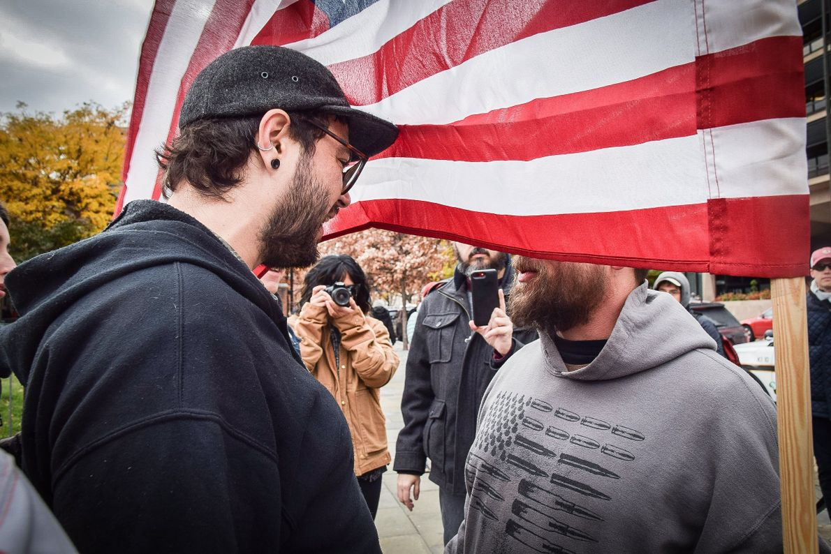Two individuals argue on either side of an American flag while others take photos during the ...