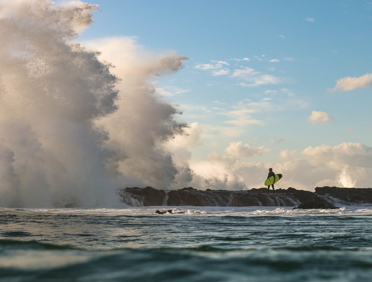 """""""A surfer waits for a break in the huge wave sets that are pounding the east ..."""