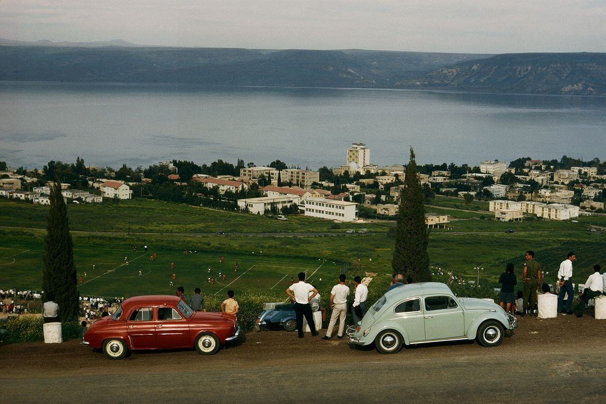 Tourists drive their cars up a hill and park to watch a game of football in ...