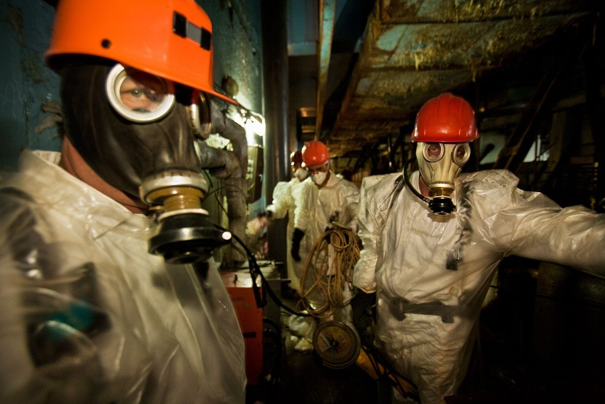 2005. Workers wearing plastic suits and respirators for protection pause briefly on their way to drill ...