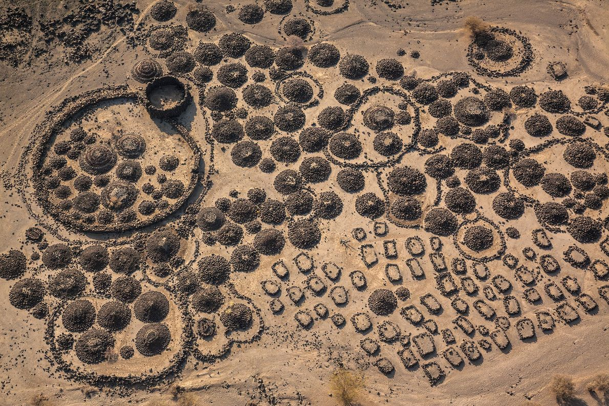 Cemeteries and camps of Afari nomads sit amidst lava flows partially buried in clay near the ...
