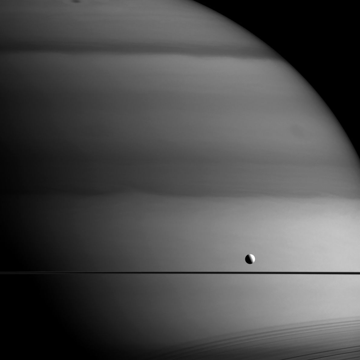Cassini took this picture in a wavelength that is absorbed by methane. Dark areas are regions ...