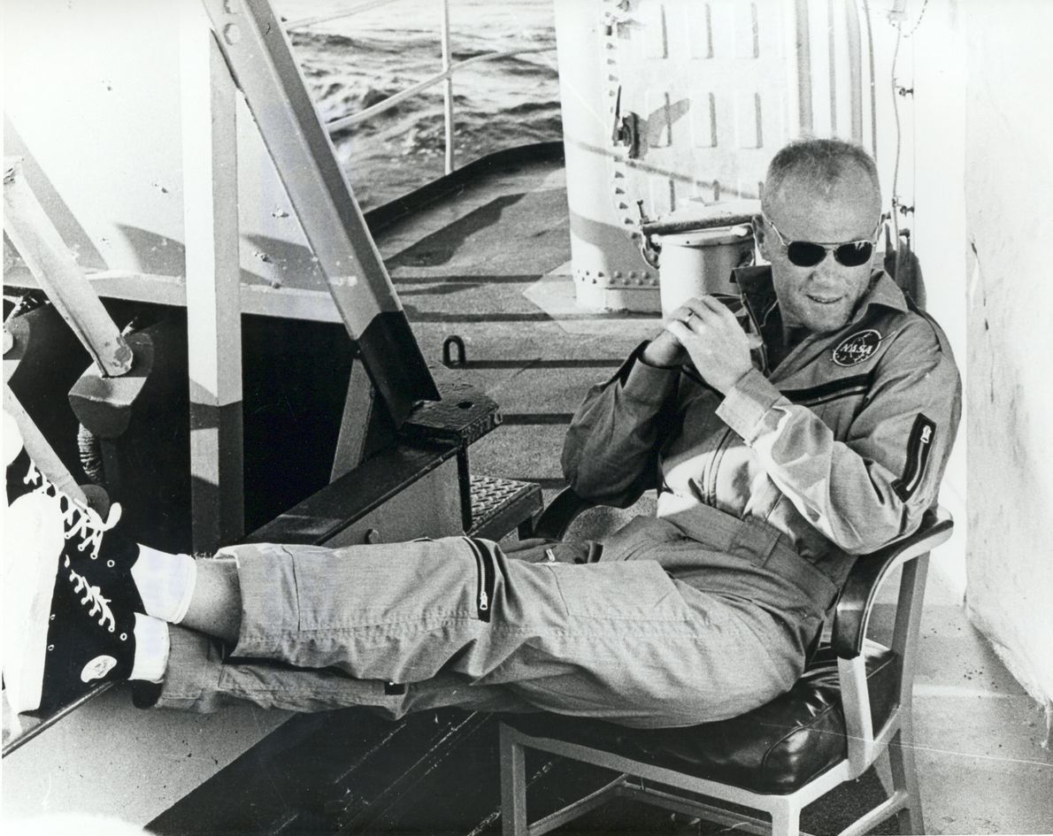 John Glenn relaxes aboard the USS Noa, having being recovered from the Atlantic after his historic ...