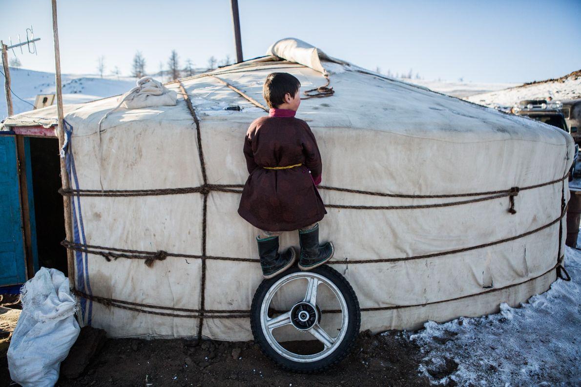 Munkhaanan plays outside his family get (yurt).