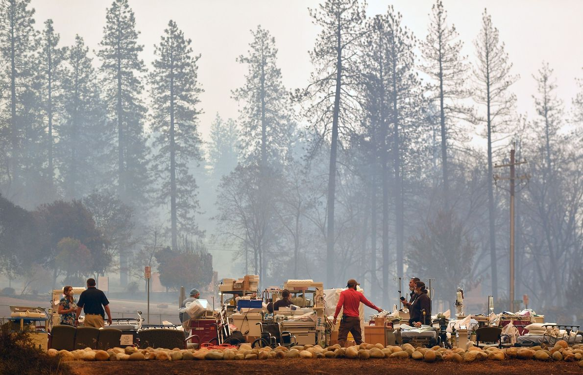 Search and rescue teams scramble to evacuate patients as the Feather River Hospital burns during the ...