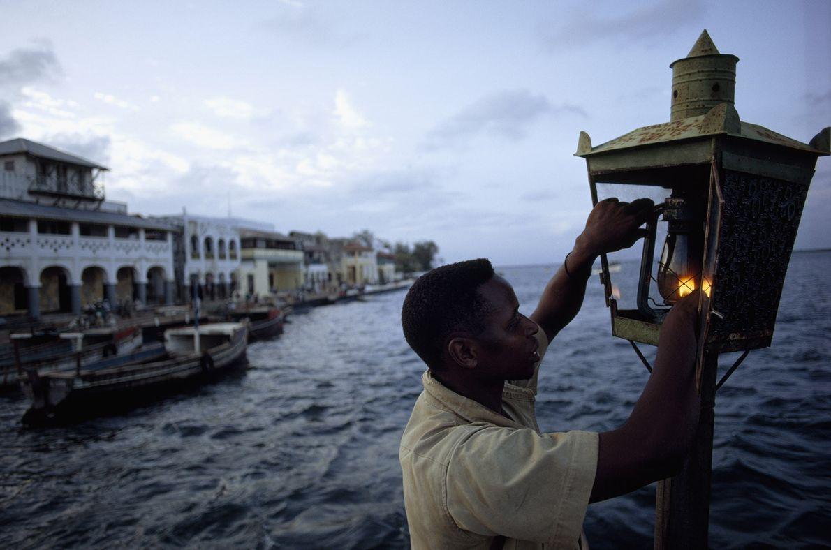 A man lights a lantern to help fishing boats find port in Lamu, Kenya, on the ...