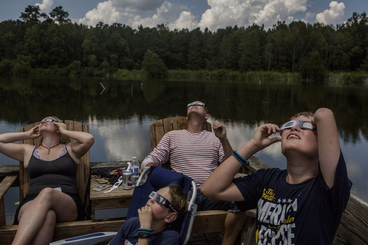 A family from Copenhagen, Denmark, watches the eclipse in Cross, South Carolina, along Lake Marion.