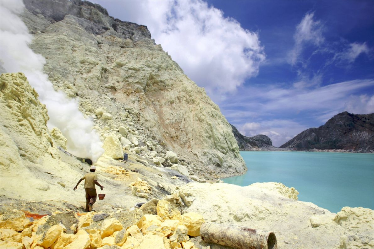 Workers mine sulphur in the crater of the Kawah Ijen volcano in the Baluran National Park ...