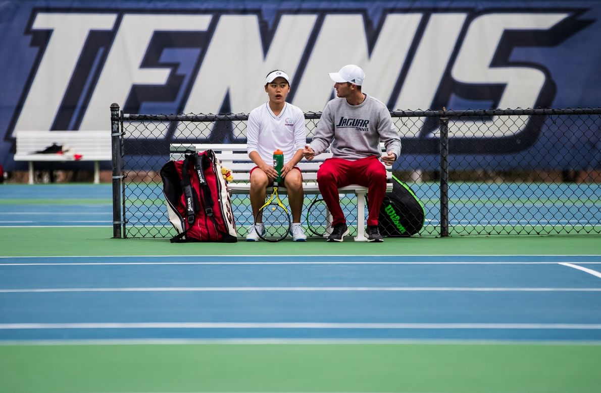 """University of South Alabama Graduate Assistant Coach, Gerhard Gruindelingh, coaches freshman varsity tennis player, Yurie Takanishi ..."