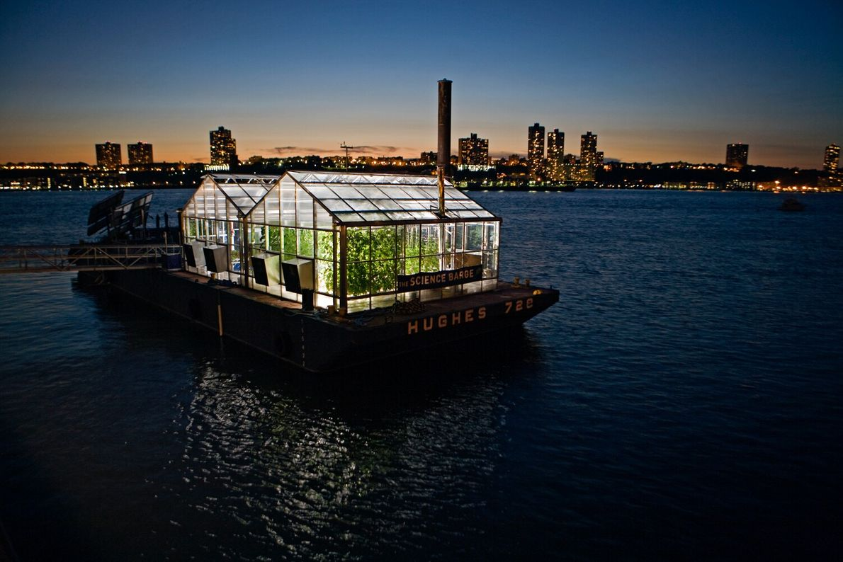 Picture of a barge with greenhouses on top of it floating on the Hudson River