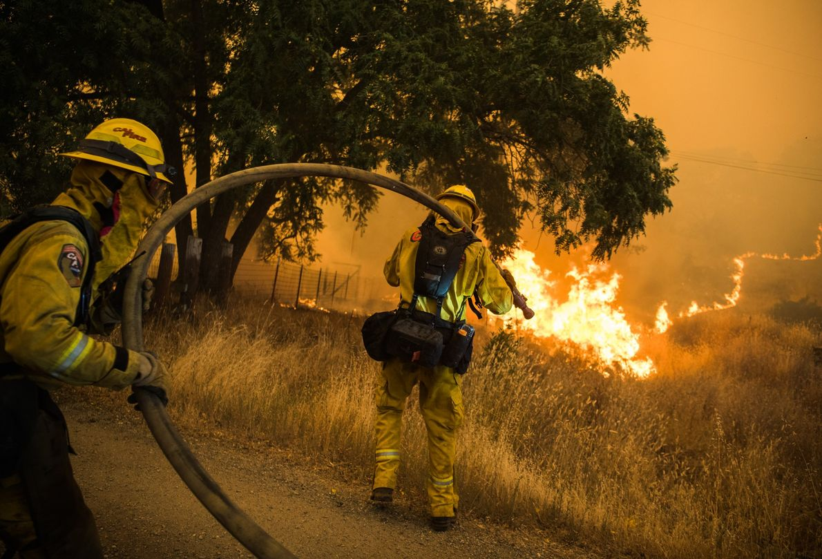 California fire firefighters work to extinguish flames as the River Fire advanced towards Lakeport, California.