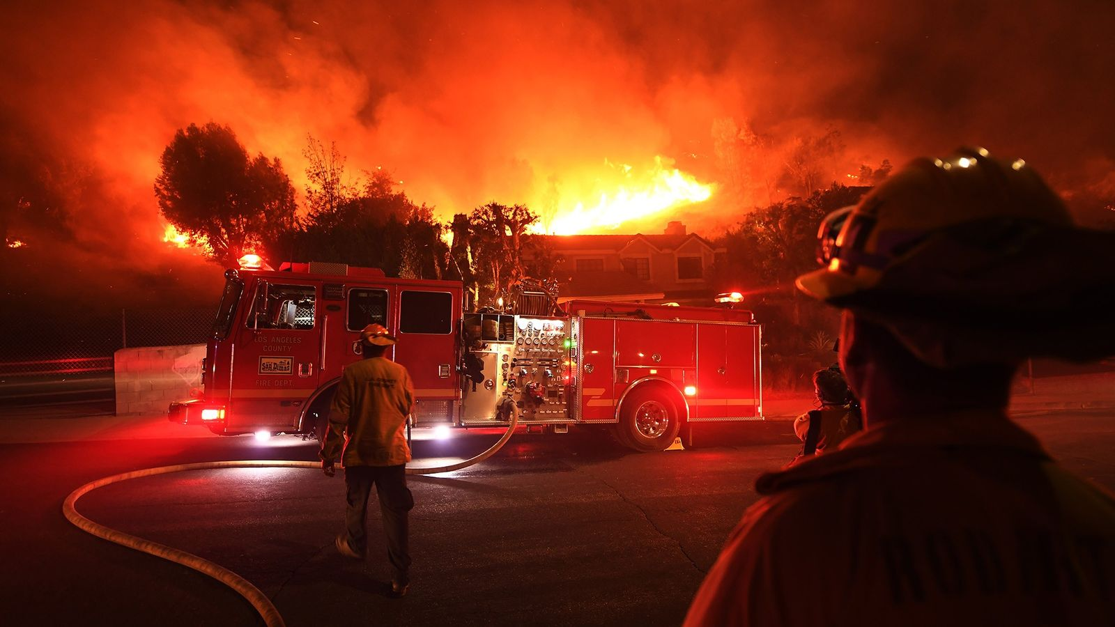Los Angeles County firefighters look on as the out-of-control Woolsey Fire explodes behind a house in ...